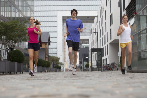 Germany, Cologne, Young man and women jogging - SKF000346