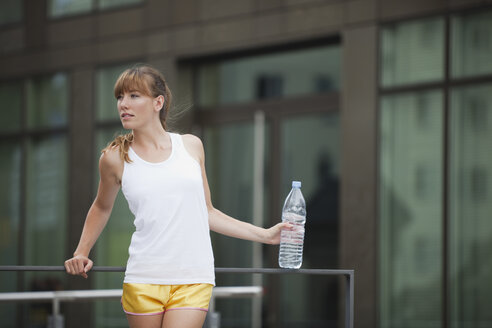 Germany, Cologne, Young woman with water bottle - SKF000358