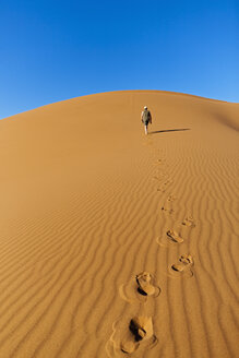 Africa, Namibia, Namib Naukluft National Park, Man walking on sand in the namib desert - FOF002478