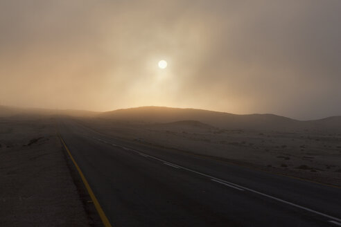 Africa, Namibia, Namib Desert, Swakopmund, View of foggy road at dawn - FOF002417