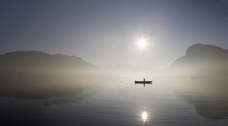 Austria, Mondsee, View of fishing boat in lake with foggy morning - WWF001678