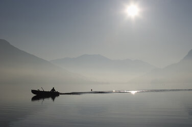 Austria, Mondsee, View of fishing boat in lake with foggy morning - WWF001681