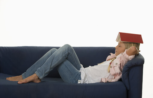 Girl (12-13 Years) resting on couch with book on head - WWF001677