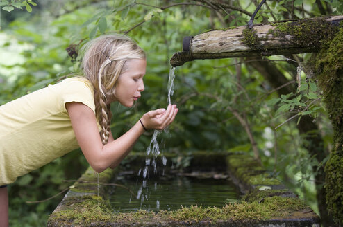 Austria, Mondsee, Girl (12-13 Years) drinking water from water spout - WWF001618