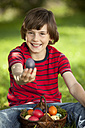Germany, Boy (10-11 Years) smiling with easter egg basket, portrait - MAEF002515