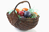 Variety of easter eggs in basket on white background - MAEF002466
