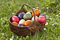 Germany, Lower Bavaria, Variety of easter eggs in basket on grass - MAEF002496