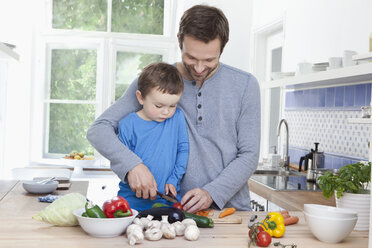 Germany, Bavaria, Munich, Father and son (2-3 Years) chopping tomato - RBF000361