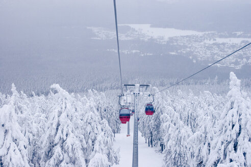 Germany, Braunlage, Cable cars above snow covered forest - HKF000342