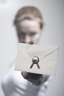 Germany, Vechelde, Woman showing sealed envelope - HKF000344
