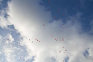 Germany, Red heart shape balloons with messages in sky - HKF000287