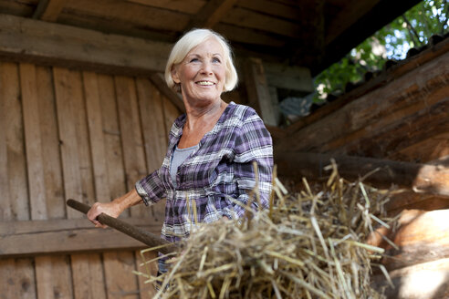 Germany, Saxony, Senior woman working at the farm, smiling - MBF001054