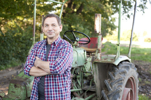 Germany, Saxony, Mature man standing by tractor, smiling - MBF001069