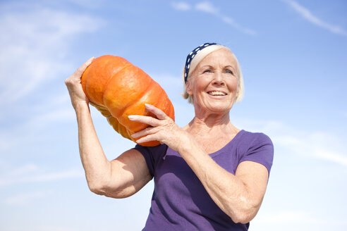 Germany, Saxony, Senior woman carrying pumpkin on shoulder - MBF001113