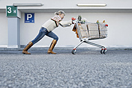 Germany, Young woman pushing shopping cart - WBF000601