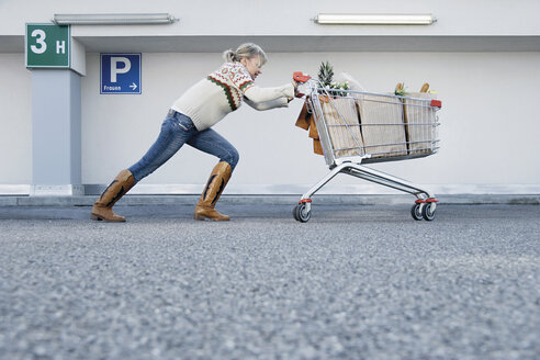 Germany, Young woman pushing shopping cart - WBF000601