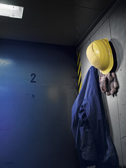 Germany, Work glove, protective workwear and safety helmet hanging in cabin - WBF000410