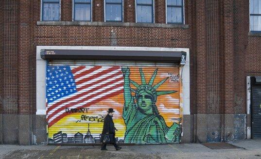 USA, New York, Man walking in front of patriotic graffitti on shutter - HK000337