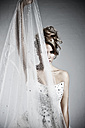 Young bride in modern dress holding net in front of face, portrait - MF000429