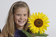 Girl (10-11 Years) with sunflower, smiling, portrait - CRF001933