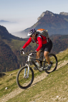 Austria, Tirol, Female mountain biker biking on spitzstein mountain - FFF001131