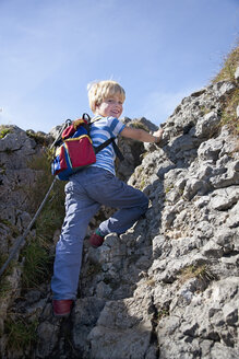 Germany, Bavaria, Boy (4-5 Years) climbing mountain, smiling, portrait - HSIF000026