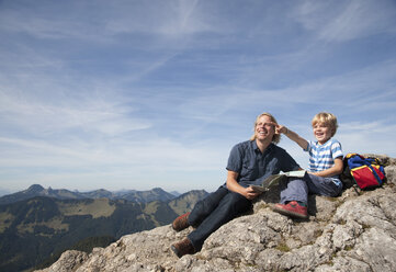 Germany, Bavaria, Father and son (4-5 Years) looking away with map on mountain summit - HSIF000020