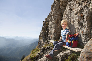 Germany, Bavaria, Boy (4-5 Years) sitting on mountain summit, smiling, portrait - HSIF000012