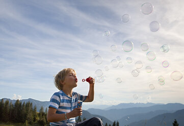 Germany, Bavaria, Boy (4-5 Years) blowing soap bubbles - HSIF000006