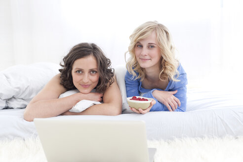 Germany, Leipzeg, Young women with laptop, smiling, portrait - MBF001142