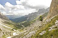 Italy, Dolomites, Mature man hiking at Rosengarten mountains - RNF000551