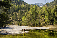 Germany, Bavaria, Garmisch, Mountain biker standing by lake - RNF000568
