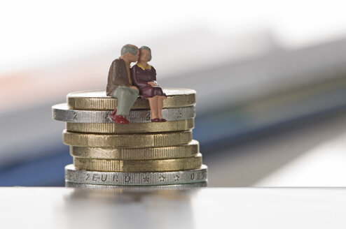 Couple figurines sitting on coin tower and kissing - ASF004188