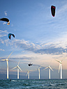 Croatia, Zadar, Kitesurfer jumping in front of wind turbine - HSIF000059