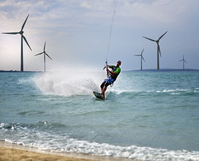 Croatia, Zadar, Kitesurfer jumping in front of wind turbine - HSIF000055