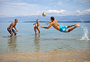 Croatia, Zadar, Friends playing volley ball at beach - HSIF000049