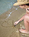 Croatia, Zadar, Young woman drawing heart-shaped on sand at beach - HSIF000044