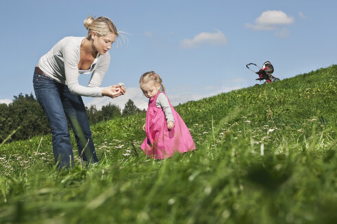 Germany, Cologne, Mother showing flower to her daughter (2-3 Years) - WESTF015634