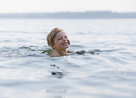 Germany, Ambach, Boy swimming in lake, smiling, portrait - HSIF000062