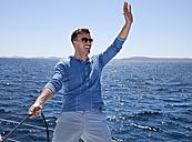 Croatia, Zadar, Young man waving from sail boat - HSIF000080