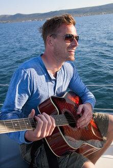 Croatia, Zadar, Young man playing guitar on sail boat - HSIF000086