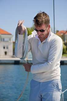 Croatia, Zadar, Young man coiling rope on sailboat in harbour - HSIF000093
