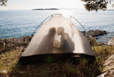 Croatia, Zadar, Young couple kissing in tent at beach - HSIF000097