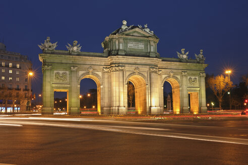 Spain, Madrid, View of Puerta de Alcalá at night with traffic - RUEF000590
