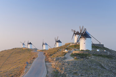 Spain, Toledo Province, Castile-La Mancha, Row of windmills with rural road at sunrise - RUEF000611