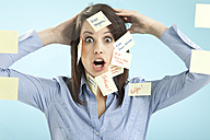 Businesswoman with adhesive notes on her face - MAEF002678