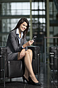 Germany, Bavaria, Business woman with mobile, smiling, portrait - MAEF002693