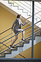 Germany, Bavaria, Business woman climbing stairscase - MAEF002756