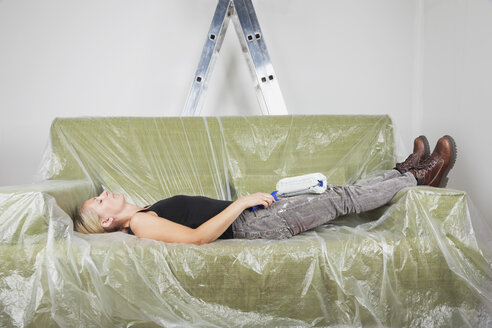 Germany, Cologne, Mature woman resting on plastic foiled sofa holding paint roller - GWF001365