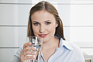 Germany, Cologne, Young woman with glass of water, smiling, portrait - PDF000115